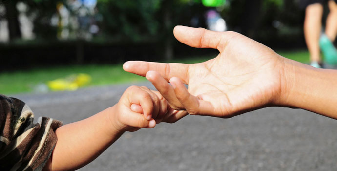child holding adult's hands