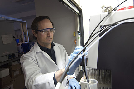 Peter Dosa wearing white lab coat and safety glasses in laboratory