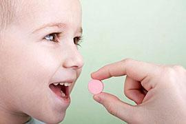 Pill being given to young boy