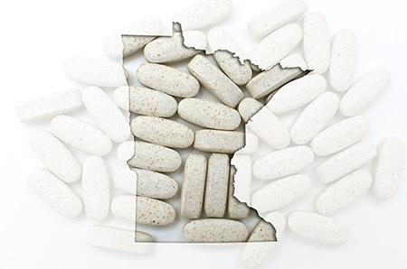 Minnesota map outline filled with pill capsules