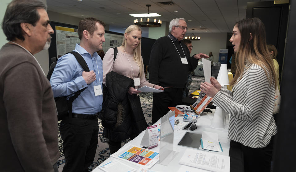 Attendees interacting with a representative from the Rare Action Network.