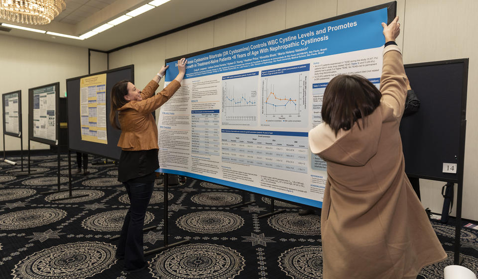 Poster presenters hanging up their research poster.