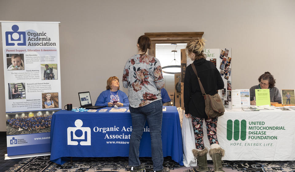 Attendees interacting with representatives from the Organic Acidemia Association and the United Mitochondrial Disease Foundation