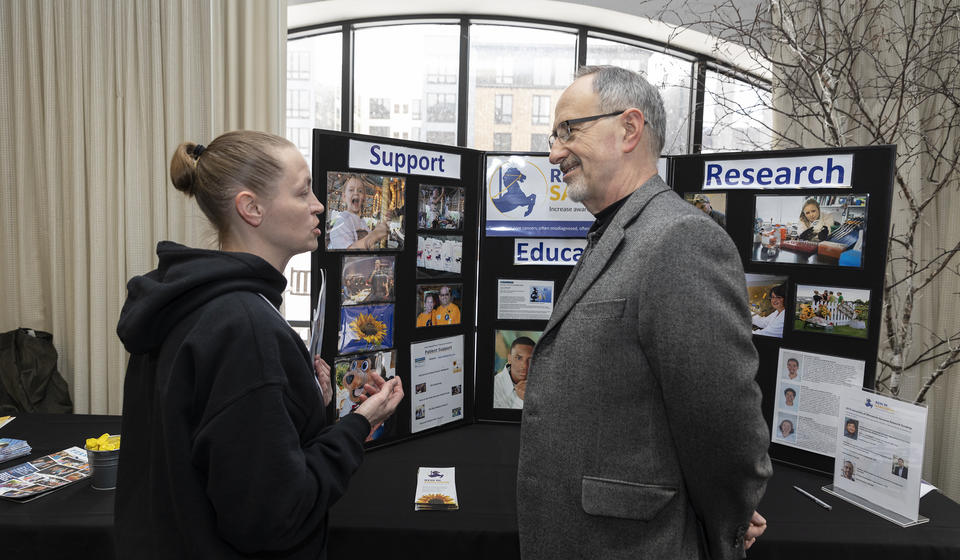 Attendee interacting with a representative from the Rein in Sarcoma Foundation.