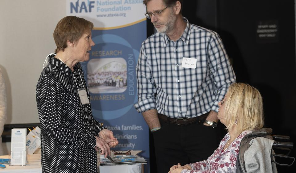 Attendees interaction with a representative from the National Ataxia Foundation.