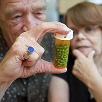 two people looking at prescription bottle